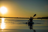 Silhouette of adult male kayaking at sunset