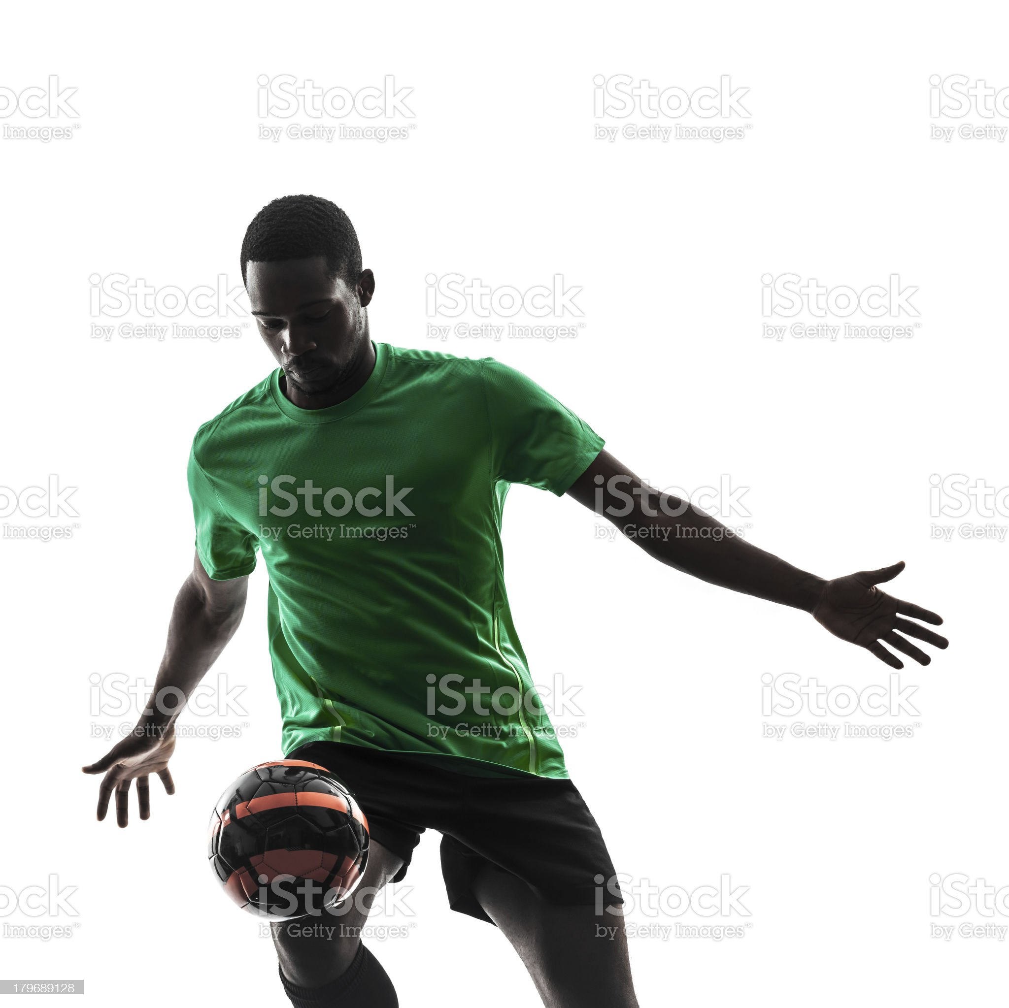Silhouette of African man juggling soccer ball royalty-free stock photo