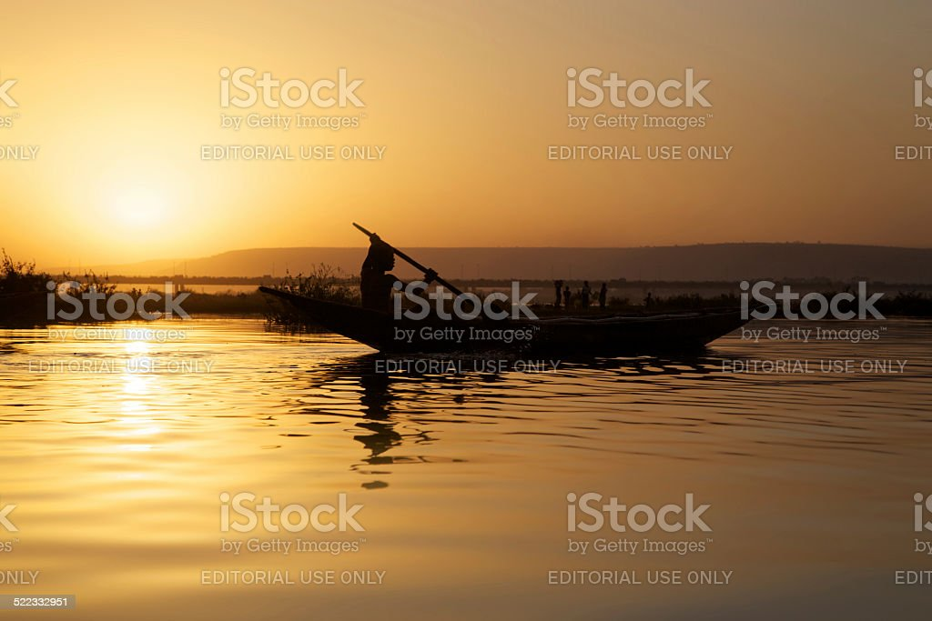 Silhouette of african man traveling on his small wooden boat stock photo