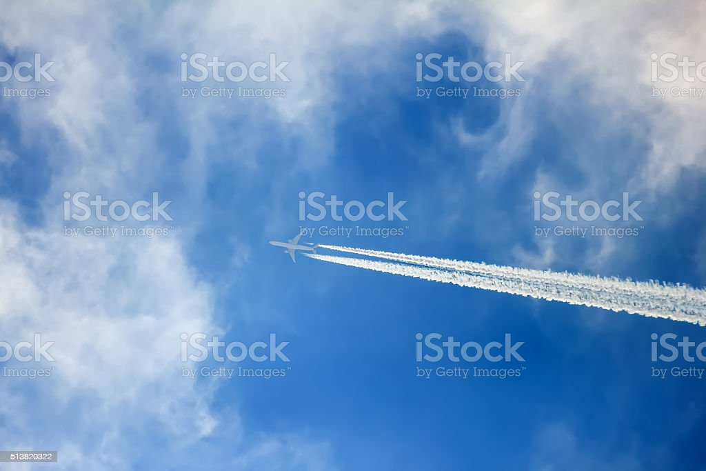 Silhouette of aircraft flying in the clouds and leaving contrail stock photo