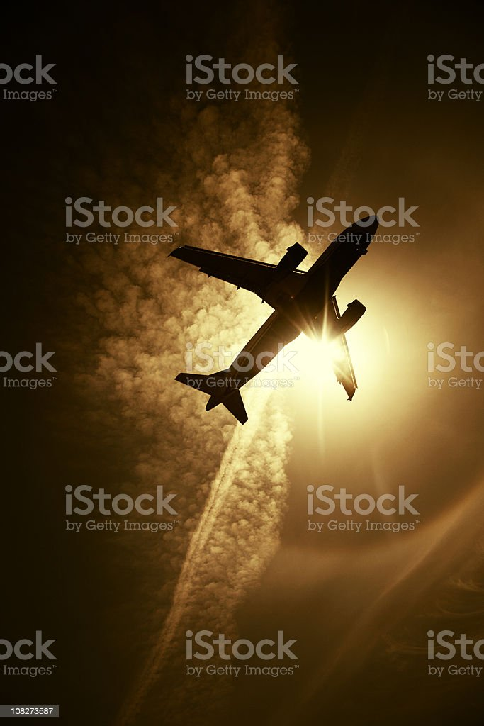 Silhouette of Airplane Flying in Sky, Toned royalty-free stock photo