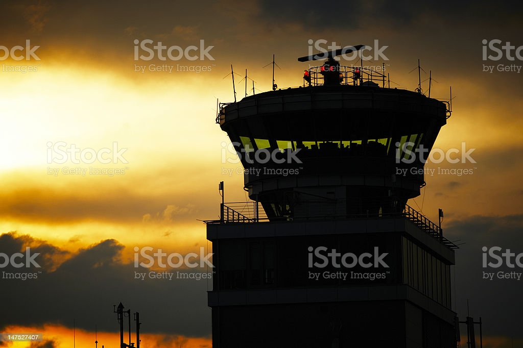 Silhouette of airport control tower at dusk stock photo