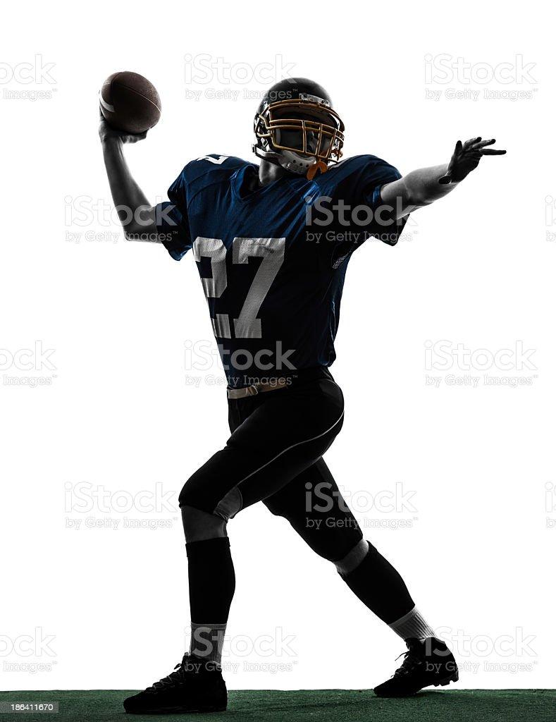 Silhouette of American quarterback throwing football stock photo