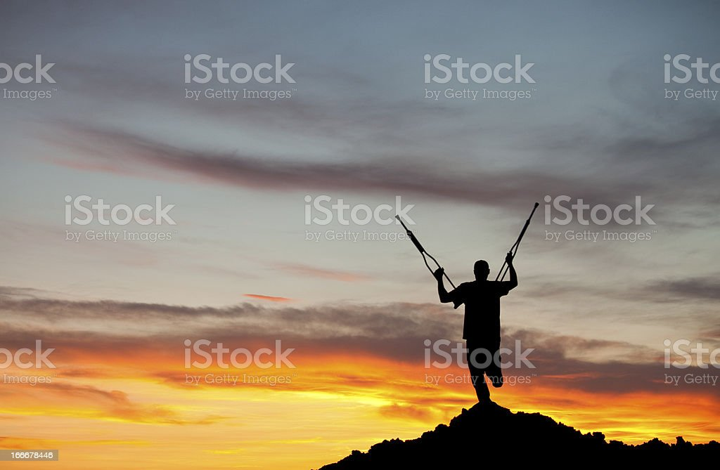 Silhouette of an Amputee With Crutches Raised royalty-free stock photo