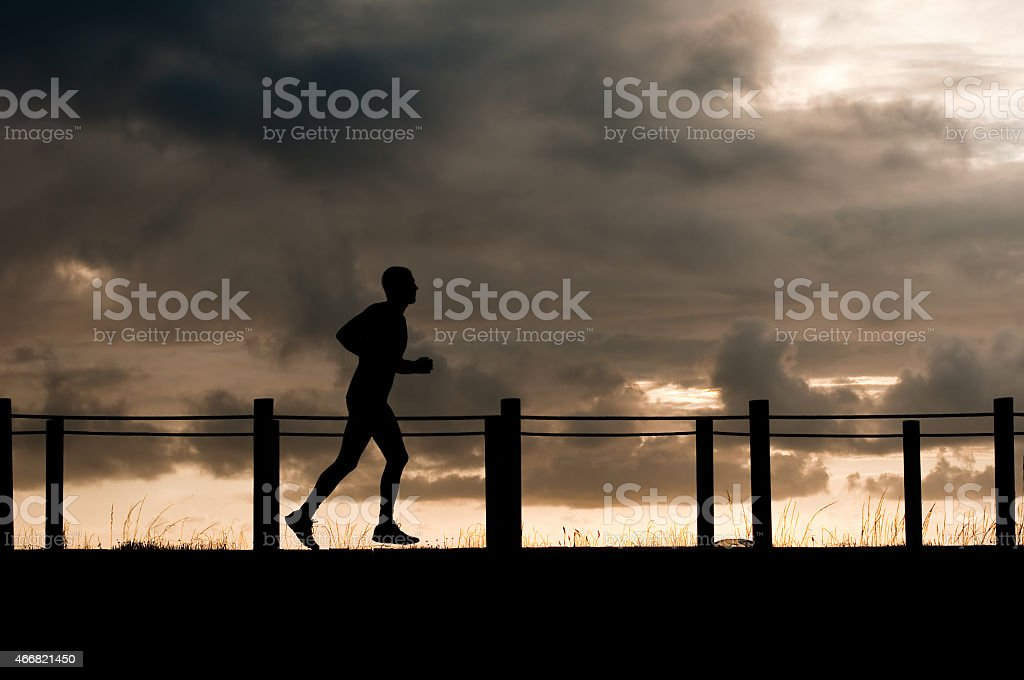 silhouette of an athlete running under a stormy sky stock photo
