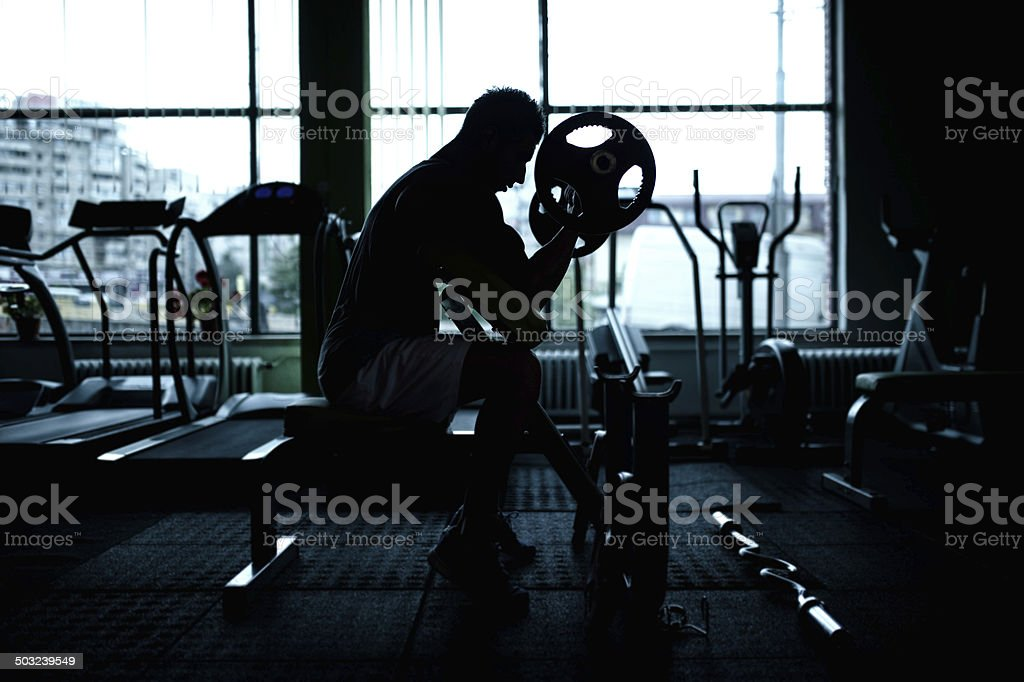 silhouette of an athletic man working out at gym. Fitness stock photo