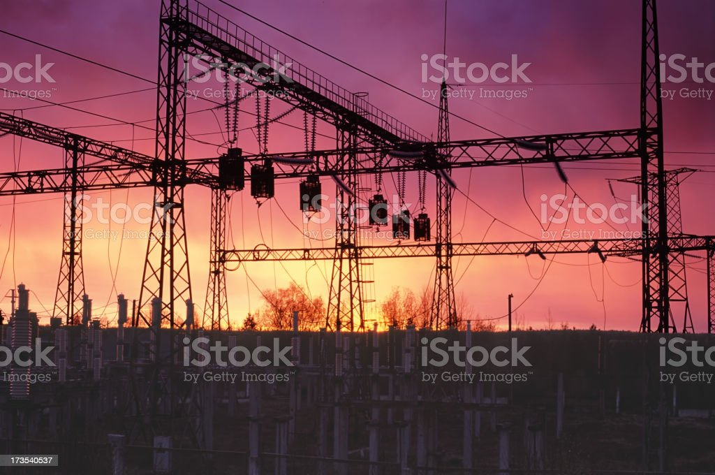 A silhouette of an energy station with a sunset background stock photo