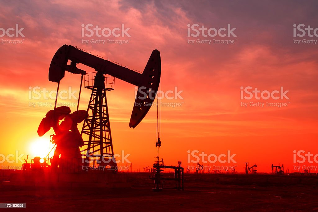 A silhouette of an oil pump in an oil field at sunset stock photo