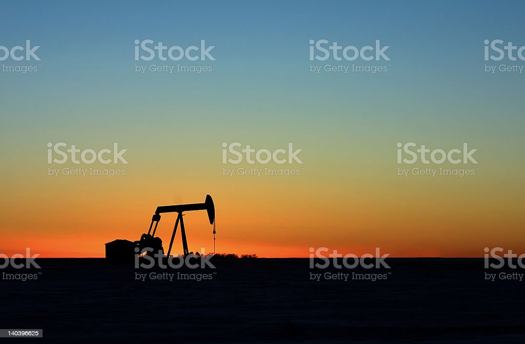 A silhouette of an oil pump landscape during a sunset royalty-free stock photo