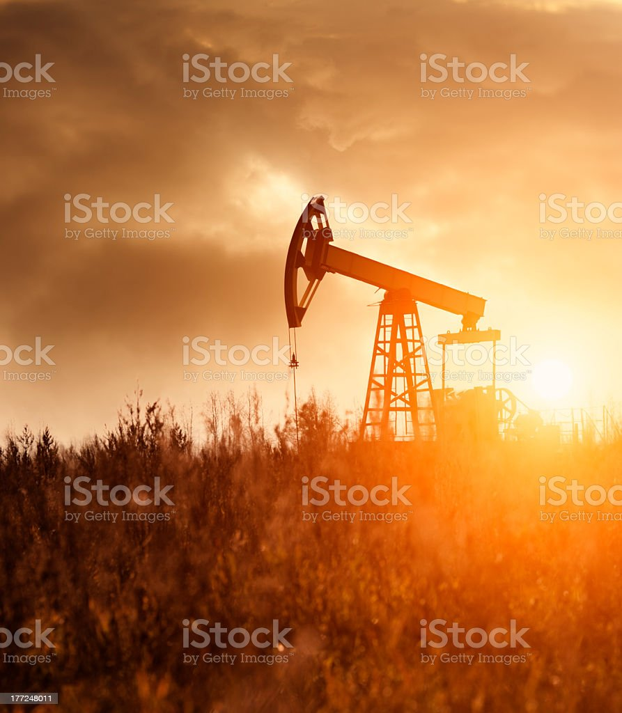 Silhouette of an oil rig in the bright sunshine stock photo