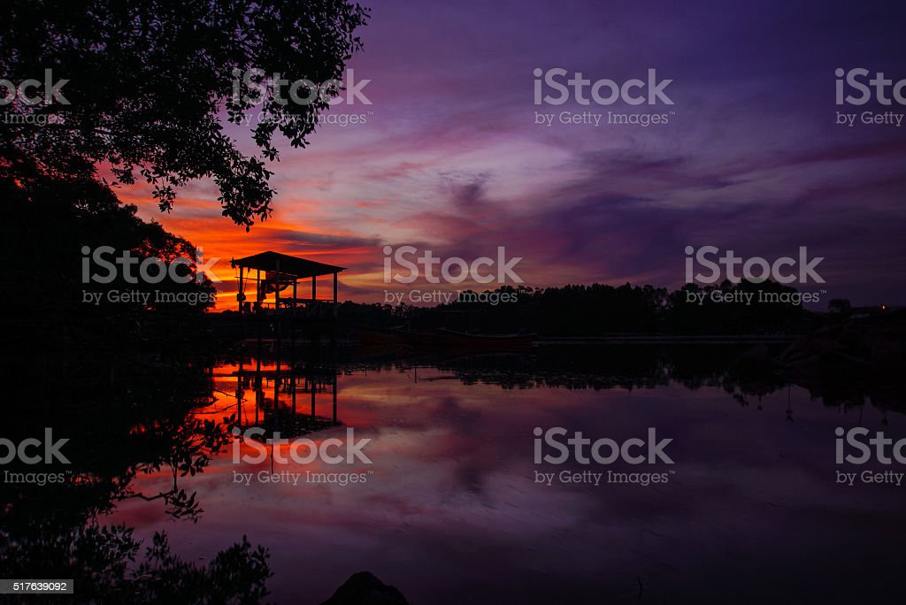 silhouette of an old jetty at sunset stock photo