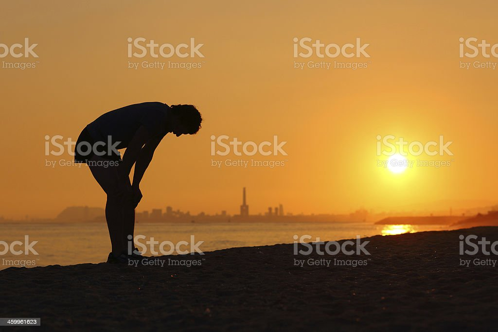 Silhouette of an tired sportsman at sunset stock photo