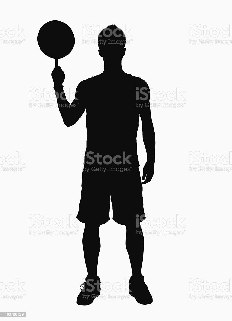 Silhouette of athlete spinning basketball on finger. stock photo