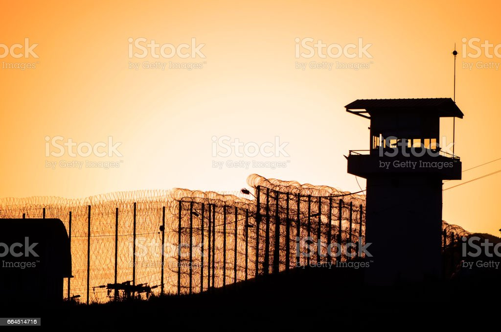 Silhouette of barbed wires and watchtower of prison. stock photo