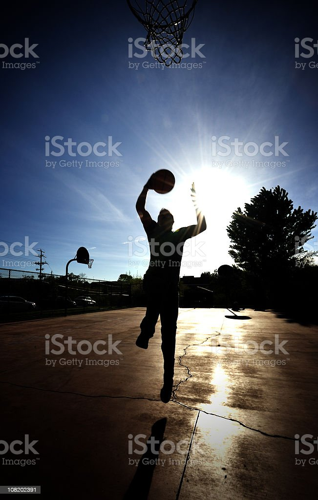 Silhouette of Basketball Player Jumping on Court royalty-free stock photo