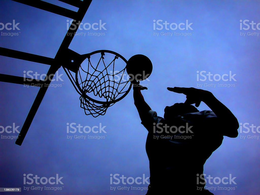 Silhouette of basketball player shooting a hoop stock photo