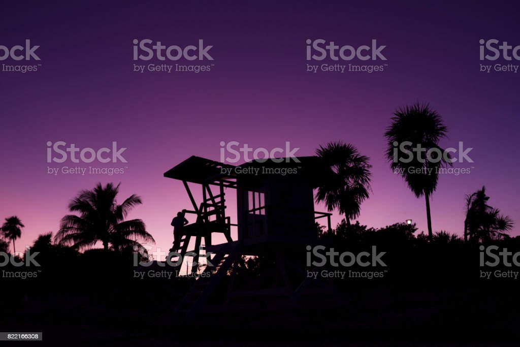 Silhouette of baywatch tower and palm trees at sunset stock photo