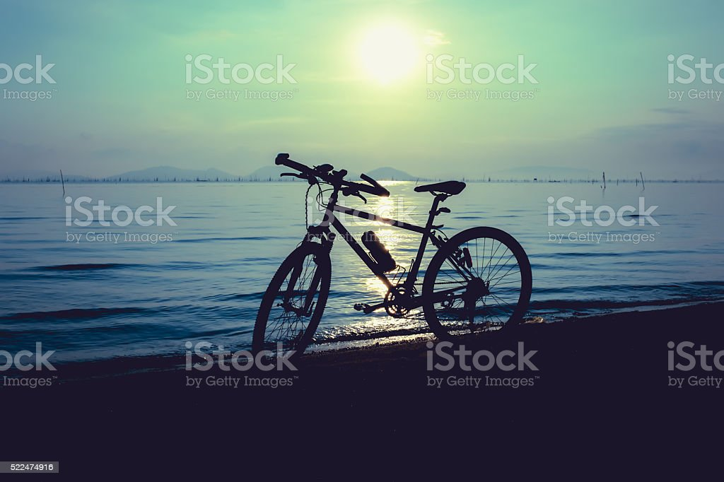 Silhouette of bicycle on beach against colorful sunset. stock photo