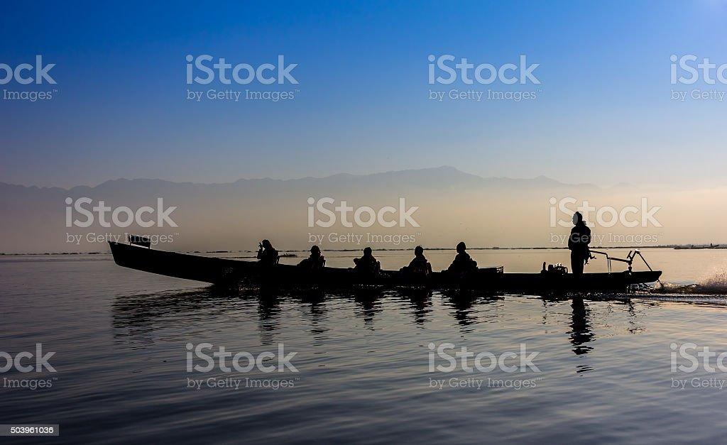Silhouette of boat at sunset Inle Lake Burma Myanmar stock photo