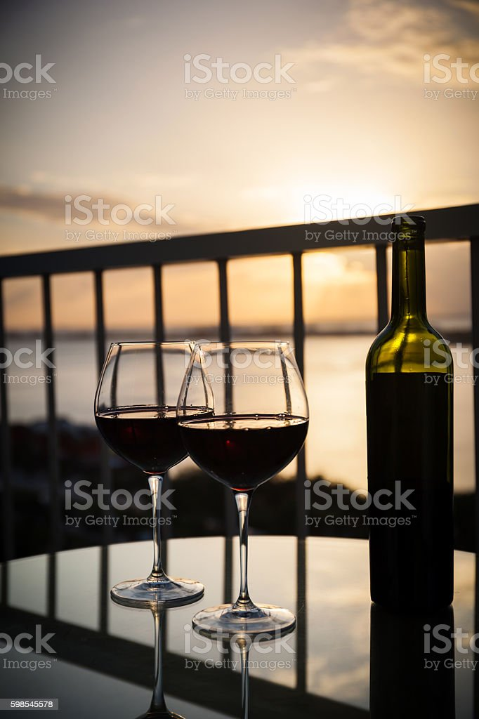 Silhouette of bottle and glasses with red wine in sunset stock photo