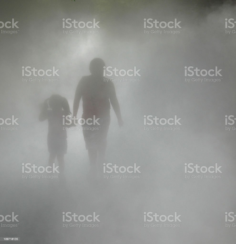 Silhouette of Boy and Little Girl Holding Hands in Fog royalty-free stock photo