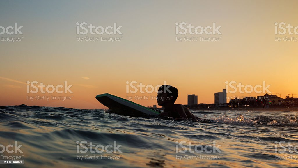 Silhouette of boy body boarding in ocean at sunset stock photo