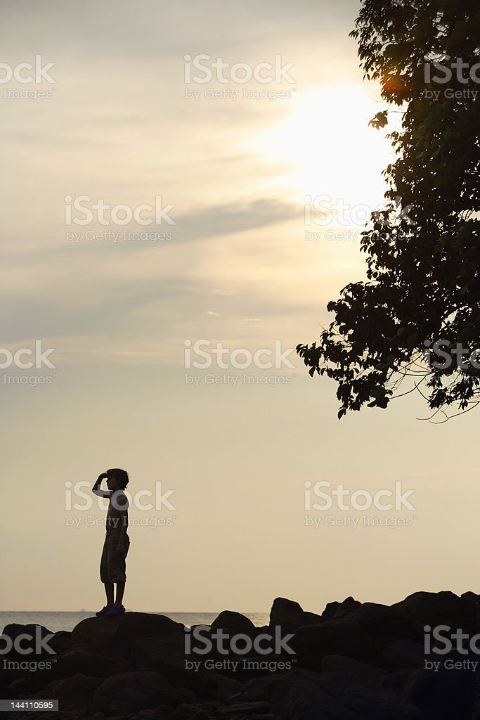 Silhouette of boy looking out to sea stock photo