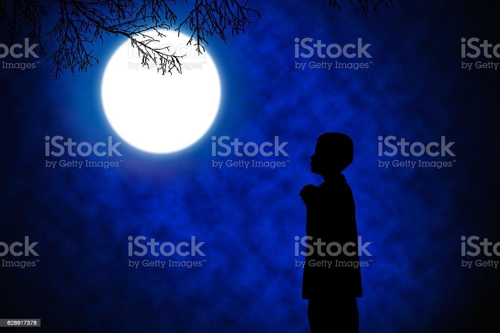 Silhouette of boy praying . stock photo
