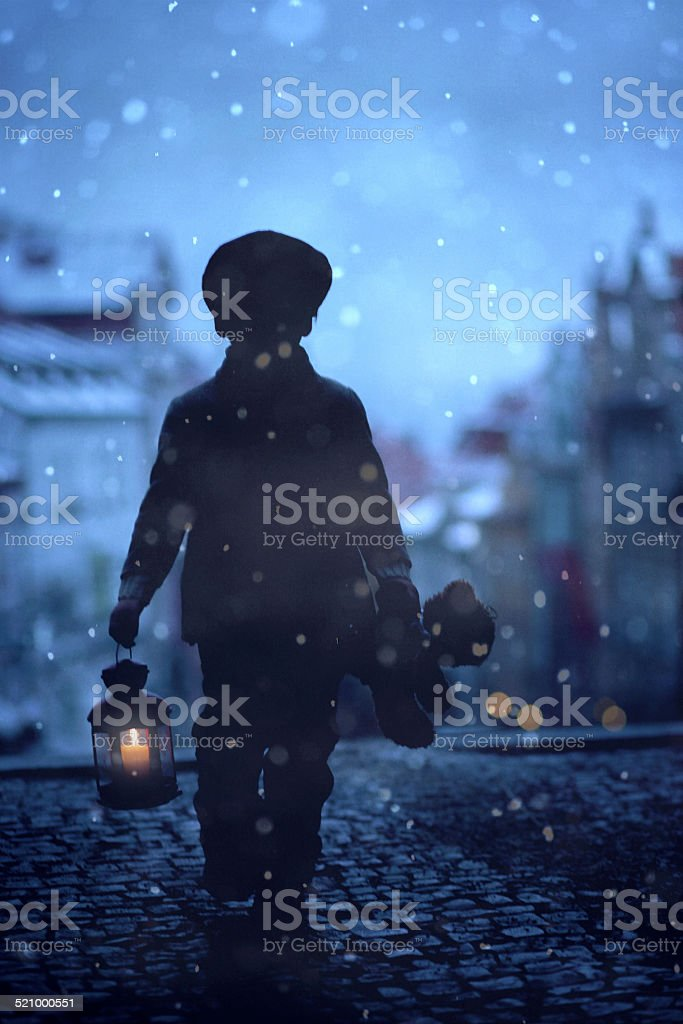 Silhouette of boy, standing on stairs, holding lantern and teddy stock photo