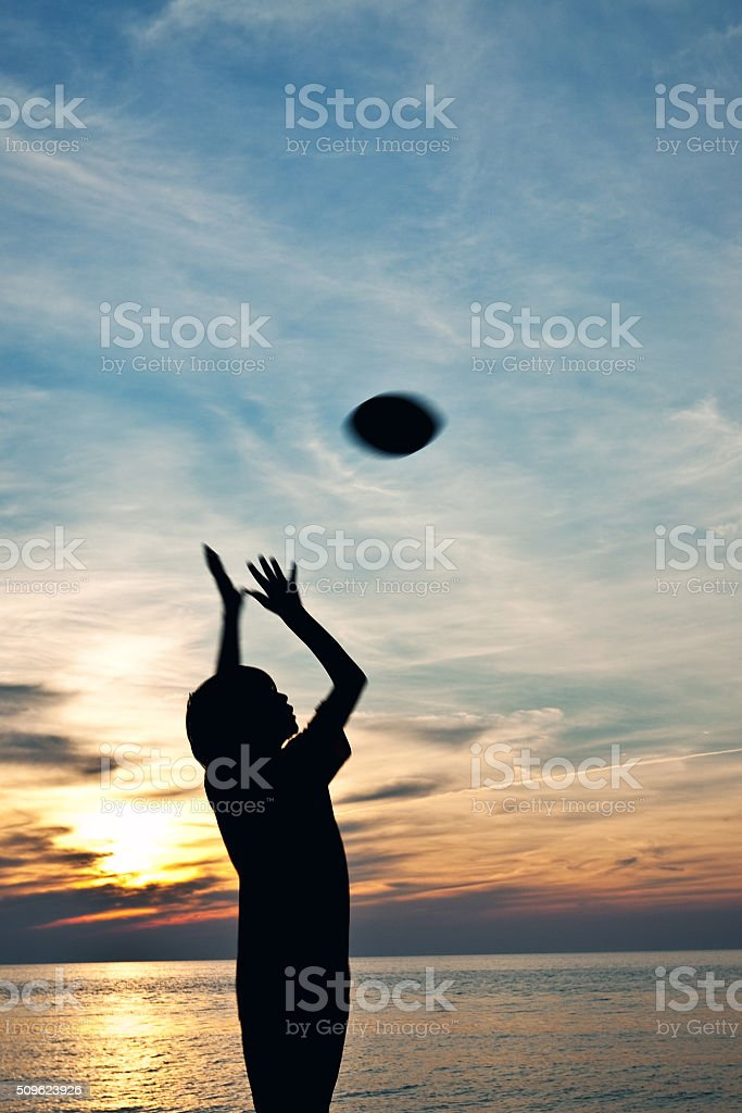 Silhouette Of Boy Throwing Football On Beach stock photo