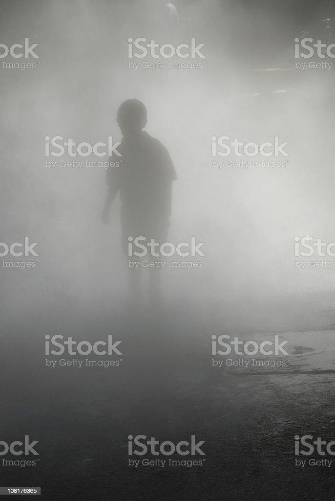 Silhouette of Boy Walking Through Heavy Fog stock photo
