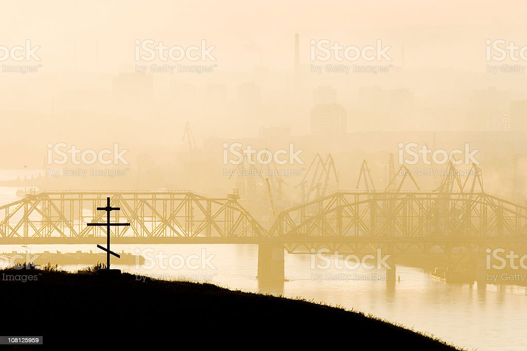 Silhouette of Bridge Over River and Orthodox Cross on Hill royalty-free stock photo