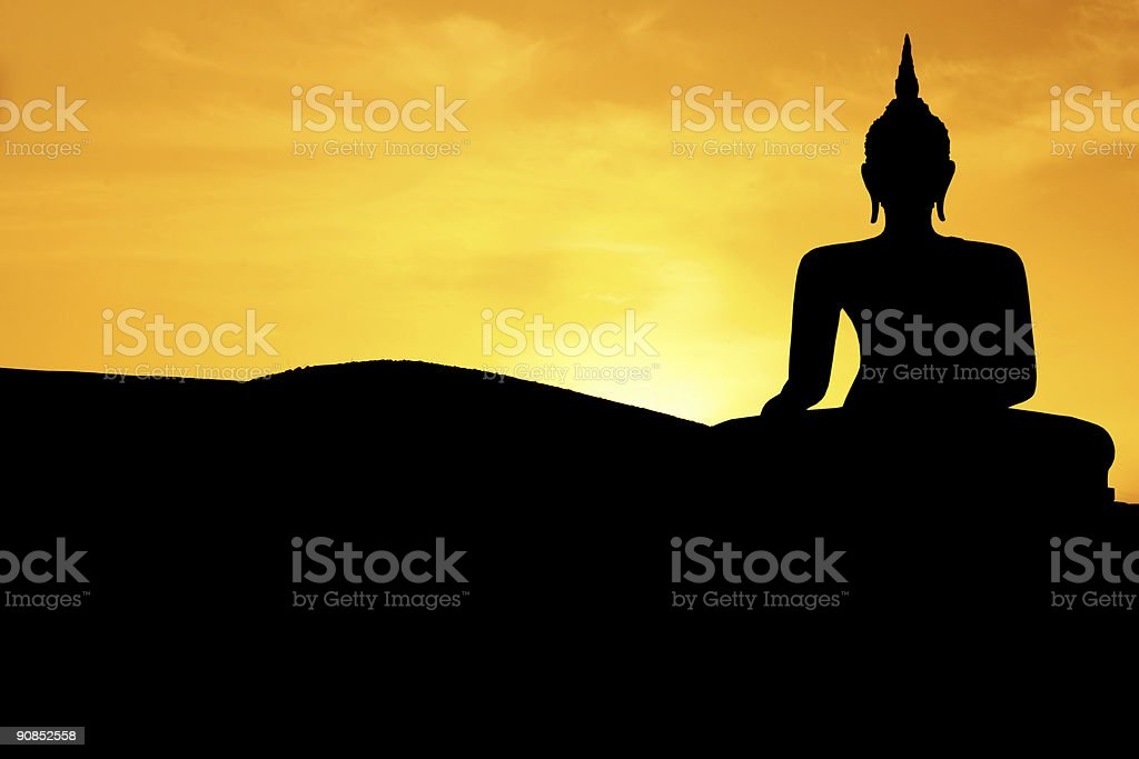 Silhouette of Buddha against a yellow sunset royalty-free stock photo