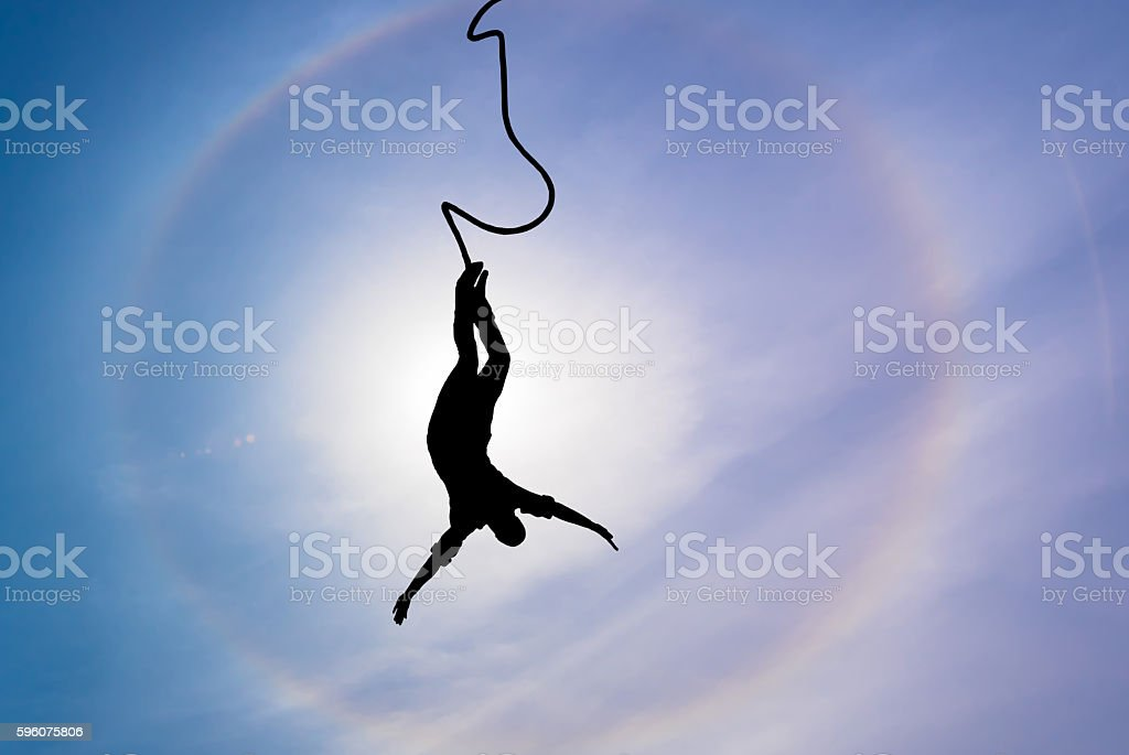 Silhouette of bungee jumper over blue sky background stock photo
