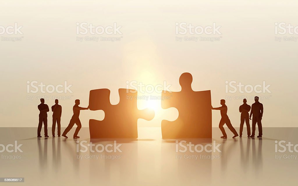 Silhouette of business men merging and solving puzzle stock photo