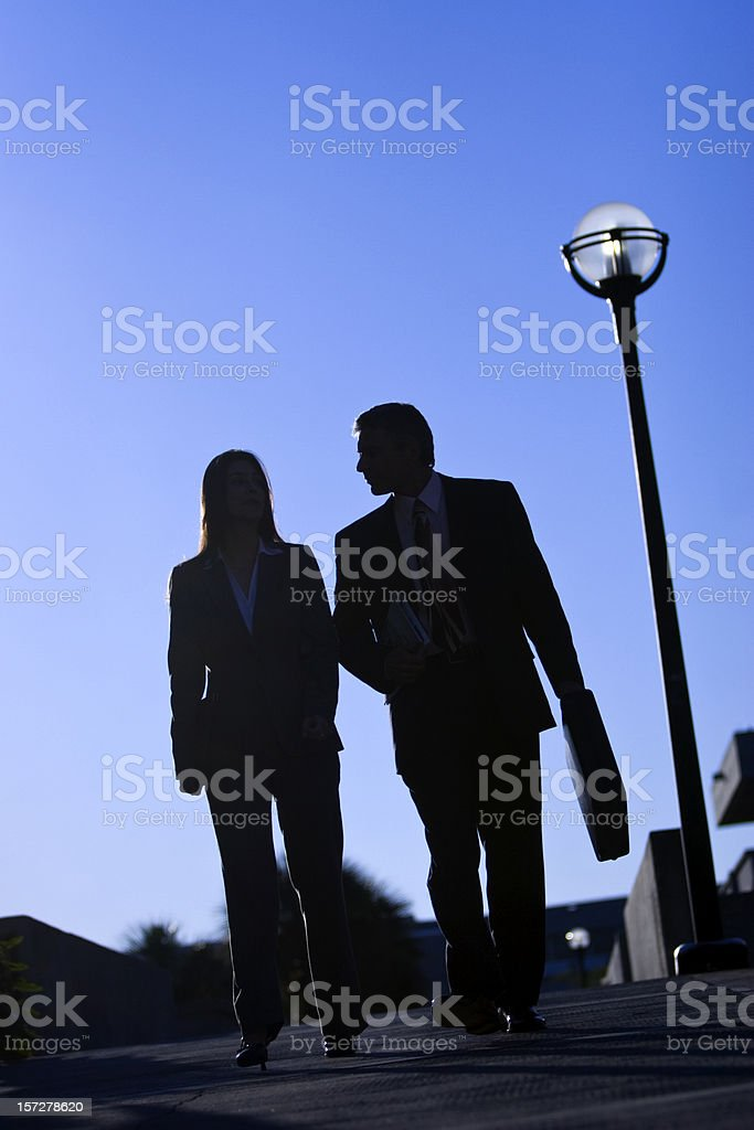 Silhouette of businessman and businesswoman walking stock photo