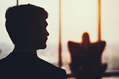 Silhouette of businessman in front of office window