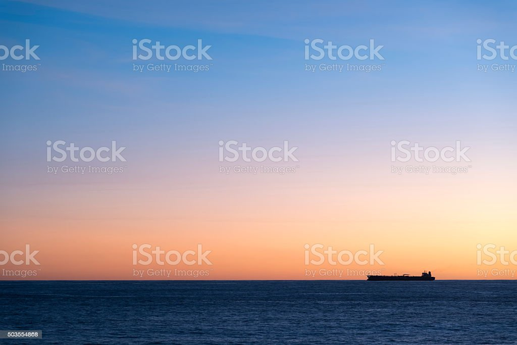 Silhouette  of cargo ship on the horizon stock photo