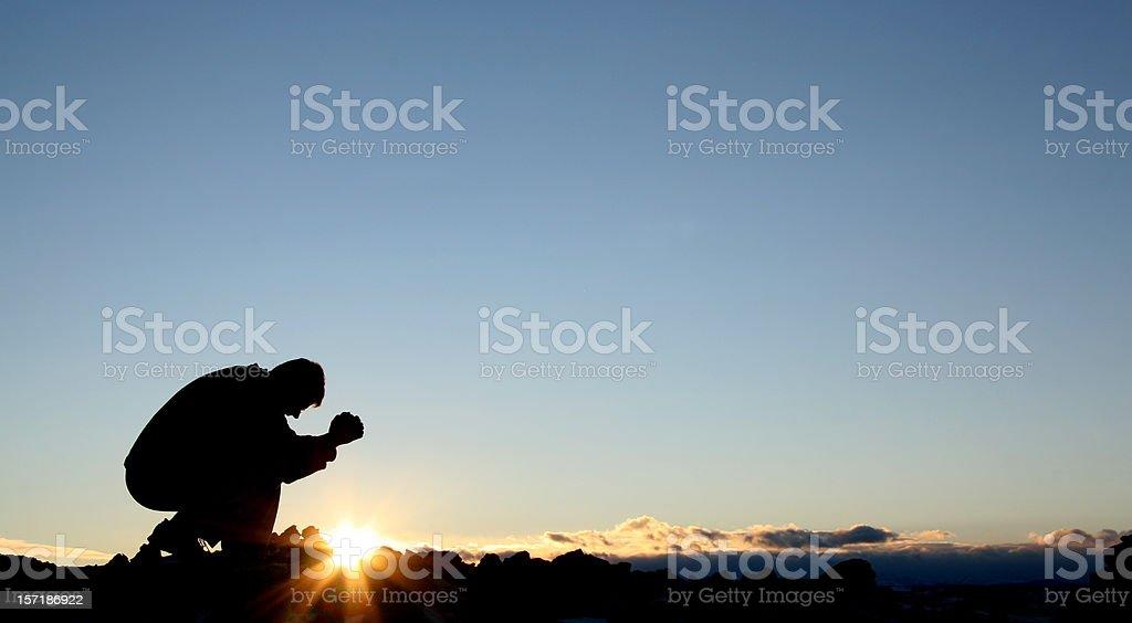 Silhouette of Caucasian Male Praying stock photo