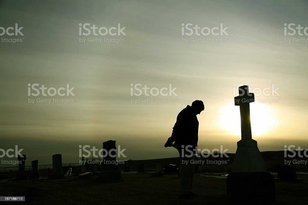 Silhouette of Caucasian Man Mourning at Graveyard stock photo