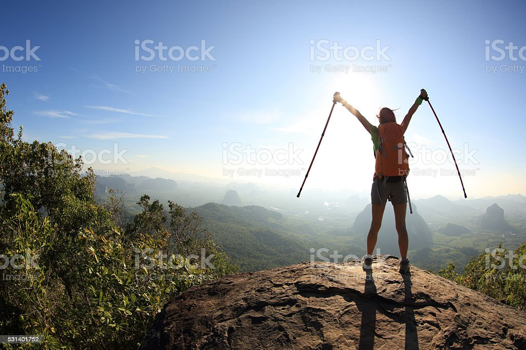 silhouette of cheering woman hiker open arms at mountain peak stock photo