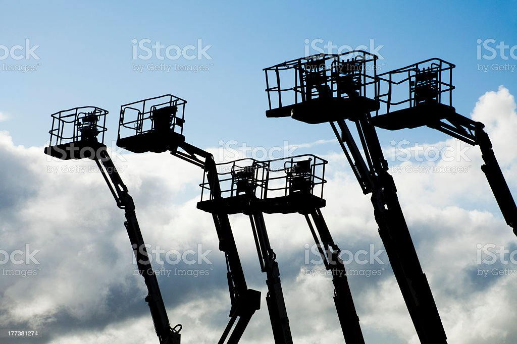 Silhouette of cherry pickers in a row stock photo