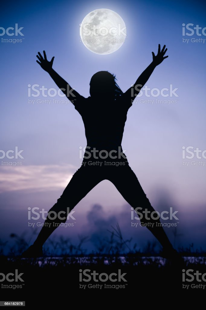 Silhouette of child enjoying and jumping at riverside. stock photo