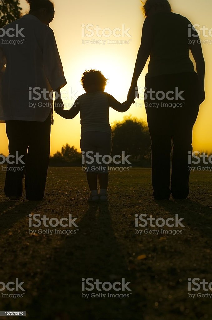 Silhouette of Child holding her mother's and grandmother's hands royalty-free stock photo