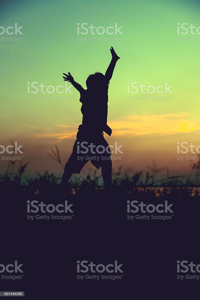 Silhouette of child jumping against sunset. stock photo