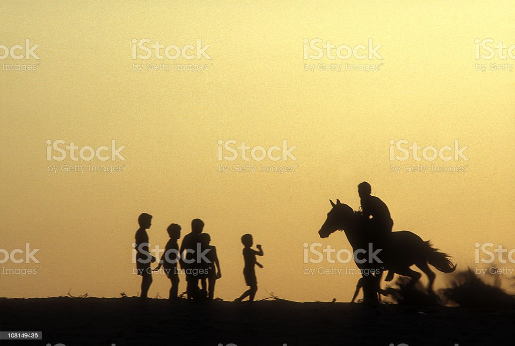 Silhouette of Children Waiting to Ride Horse at Sunset royalty-free stock photo