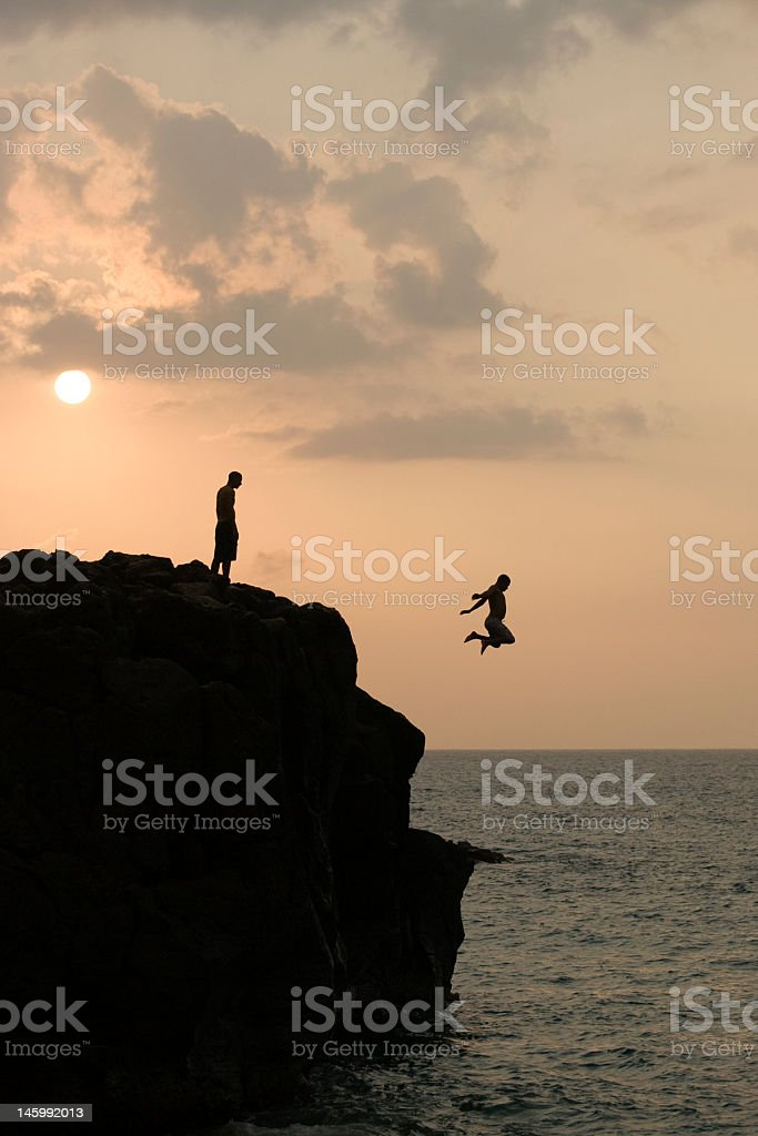 Silhouette of cliff jumpers at sunset royalty-free stock photo