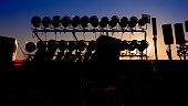 Silhouette of Concert Stage with Blue Sky and Sun Background