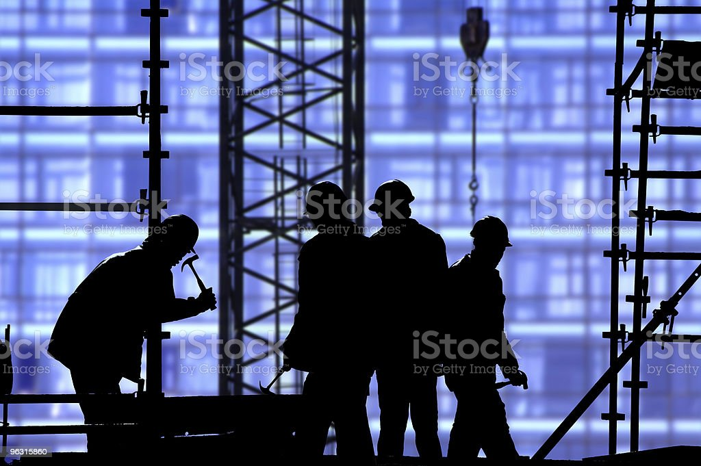 Silhouette of construction workers against blue royalty-free stock photo