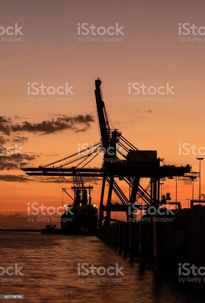 Silhouette of container cargo and crane bridge stock photo